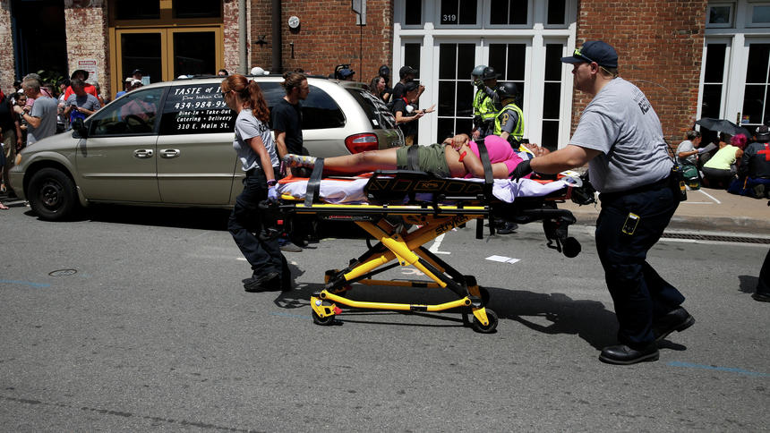 """Rescue workers transport a victim who was injured when a car drove through a group of counter protestors at the """"Unite the Right"""" rally Charlottesville"""